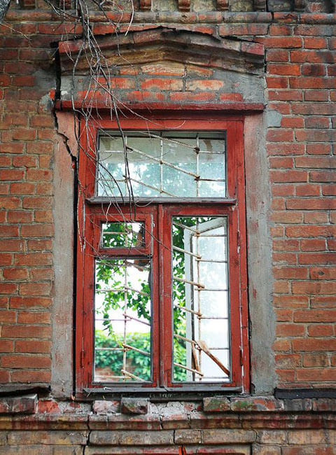Outside view of window with crumbling bricks